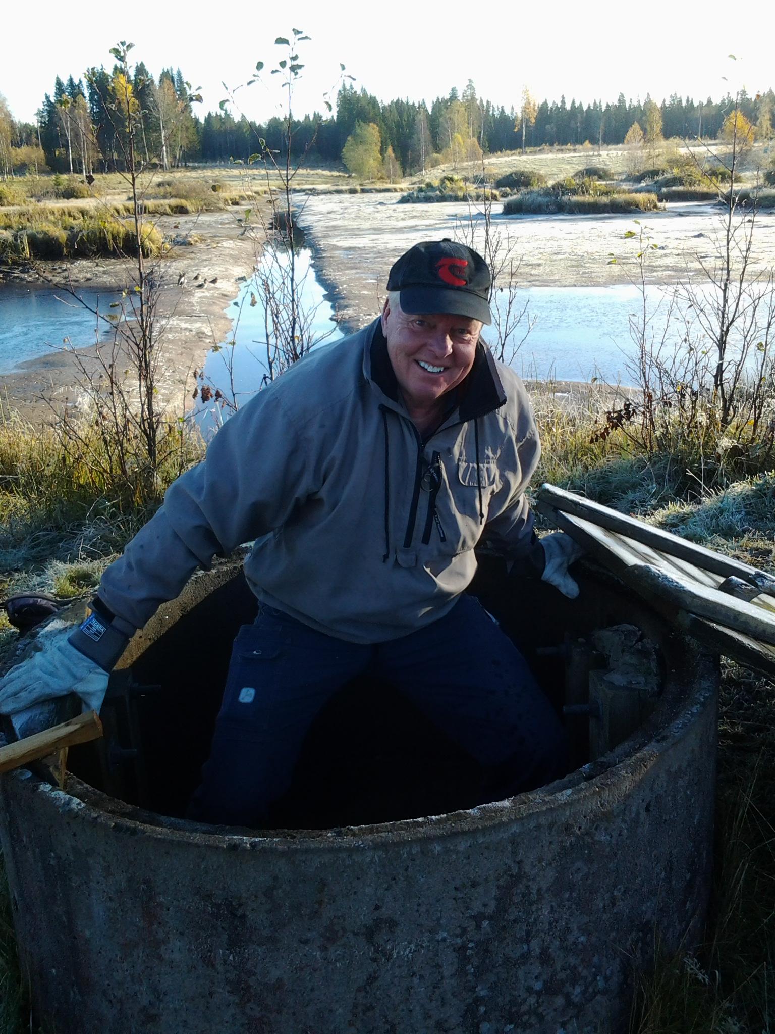 Åke Jansson klättrar ner i brunnen för att öppna sista dammluckan.