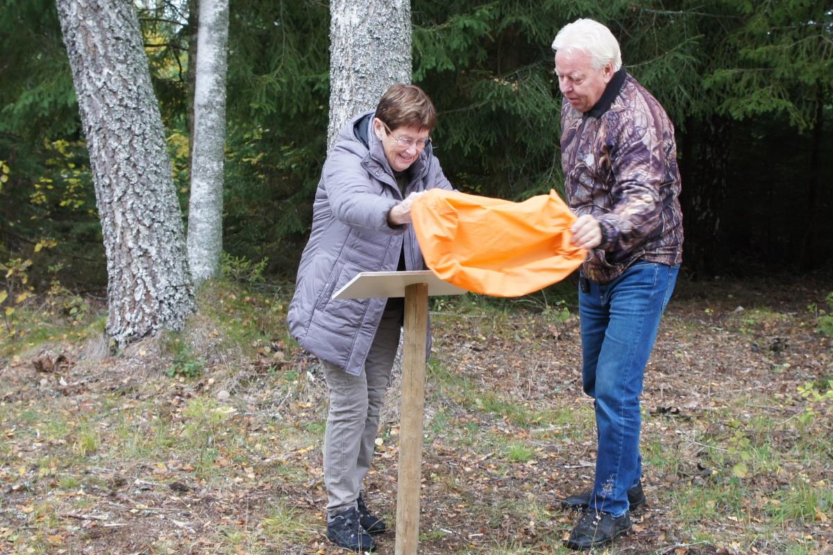 Anita Svensson avtäcker minnestavla med hjälp av Åke Jansson.